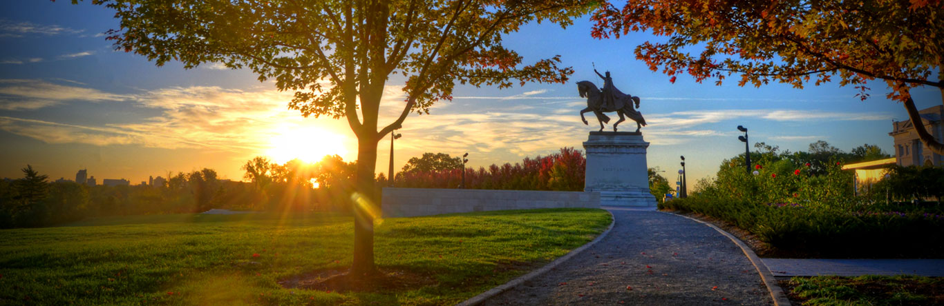 Stature of man on horse in park at sunrise