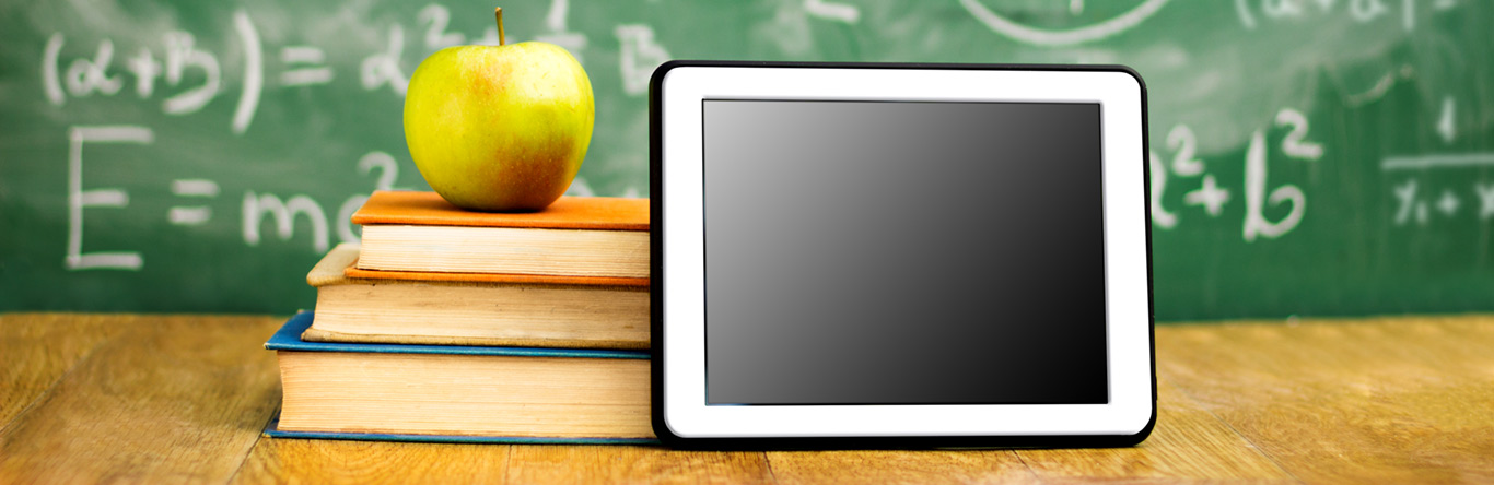 green apple on 3 books next to tablet in front of chalk board